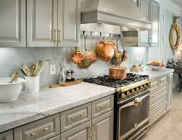 gray cabinets copper pans and pots gold accent marble countertop