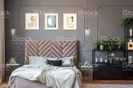 dunkel grau schlafzimmer innenraum mit vertäfelung an der wand kingsizebett mit weichen betthaupt drei plakate und metallständer mit pflanzen und