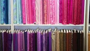 Colorful bolts of fabric on display at a sewing supply store