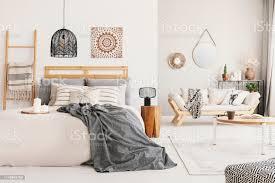 warmes ethnowohnzimmer und schlafzimmer mit beigefarbenem skandinavischem sofa und kingsizebett mit grauer decke echtes foto stockfoto und mehr bilder