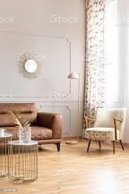 pastell rosa le in der ecke des hellen wohnzimmer interieur mit dekorativer spiegel auf wand mit formteil fenster mit vorhängen ledersofa und