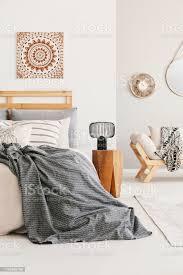 ethnografik an der wand stilvollem warmen schlafzimmer mit komfortablem bett mit grauer decke und hölzernem nachttisch mit moderner le echtes