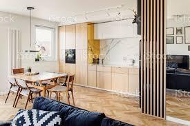 gemütlichen skandinavischen offenen raum mit küche wohnzimmer und küche mit sofa und familie tabelle helle und sonnige zimmer mit großen fenstern und