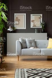 modernes sofa mit kissen und zwei malen auf eine graue wand in einem wohnzimmer interieur echtes foto stockfoto und mehr bilder asymmetrisch