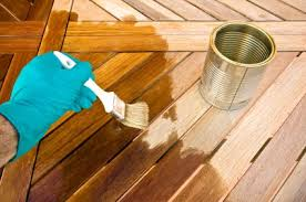 Applying Tung Oil To Cleaned And Sanded Smooth Teak Patio Table Top