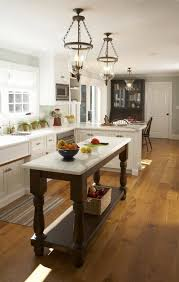 U Shaped Kitchen With Blue Gray Walls Rustic Wood Floors White Cabinets Calcutta Marble Countertops Pair Of Glass Lanterns Over Chocolate Brown