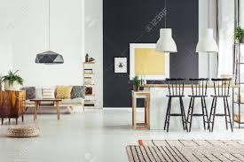 gemütliches wohnzimmer im vintage stil mit rustikalen barhockern und schicker schwarzer le