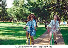Two Young Female Friends Riding Their Bicycles In The Park Cheerful Women Retro Bikes On A Summer Day