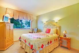 schlafzimmer mit kommode und fernseher mit grünen wänden