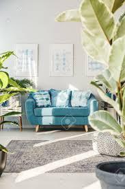 türkis sofa mit gemusterten kissen im frühjahr wohnzimmer mit teppich und plakaten