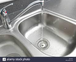 water running from tap into kitchen sink basket strainer stock