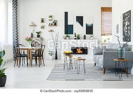 schwarze stühle am esstisch im hellen wohnzimmer mit grauem