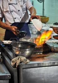 cuisiner avec un wok cuisine cuisinier asiatique avec un wok sur une flamme de gaz