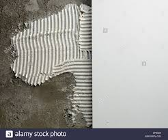 construction notched trowel mortar and tiles on cement wall stock