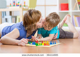 Family Child And Mom Playing Board Game At Home On The Floor
