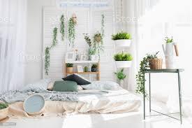 helle moderne skandinavische schlafzimmer interrior mit bett kissen plaids uhr regale grünen pflanzen in körben mockup morgen muster hintergrund
