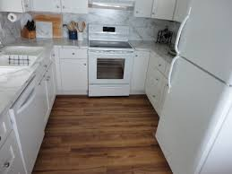 Stylish White U Shapes Kitchen Design With Hardwood Cabinetry Set On Brown Polished Vinyl Plank Flooring In Small Place Ideas