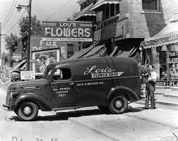 Man Loading A Floral Arrangement Into An International Model Panel Delivery Truck For Lous Flower Shop