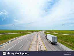 Highway Winding Between Green Plains Towards Horizon With White Semi ...