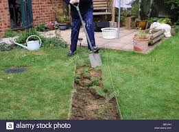 Man Digging Out Turf For New Garden Path In Modern British House ... Garden Eaging Picture Of Small Backyard Landscaping Decoration Best Elegant Front Path Ideas Uk Spectacular Designs River 25 Flagstone Path Ideas On Pinterest Lkway Define Pathyways Yard Landscape Design Ma Makeover Bbcoms House Design Housedesign Stone Outdoor Fniture Modern Diy On A Budget For How To Illuminate Your With Lighting Hgtv Garden Pea Gravel Decorative Rocks