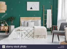 poster auf grüne wand über dem bett im schlafzimmer