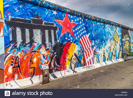 Panoramic View Of Famous Berlin Wall Decorated With Colorful Graffiti Street Art At Historic East Side Gallery On A Moody Cloudy Day In Summer