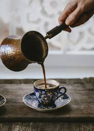 A Woman Is Pouring Turkish Coffee In To Vintage Cup