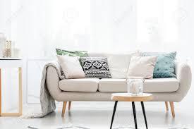 kerze in einem glasgefäß auf tabelle vor beige sofa mit kissen im wohnzimmer der skandinavischen