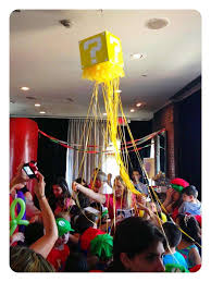 mario themed party question mark favor boxes hanging from a tree