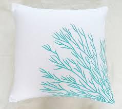 white throw pillow with aqua blue coral trellis embroidery white