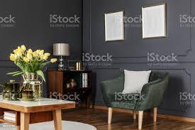 grüne sessel gegen graue wand mit plakaten im modernen wohnzimmer interieur mit blumen stockfoto und mehr bilder blume