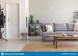 holztisch auf teppich vor grauem sofa im minimalen