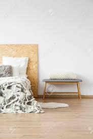 weiße strickdecke auf bank nahe bei bett mit kopierten bettlaken im natürlichen schlafzimmer mit kopienraum