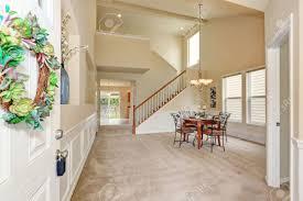 haustür zu hohen decke beige esszimmer interieur mit teppichboden und treppenhaus eröffnet elegante tabelleneinstellung und schmiedeeisernen stühlen
