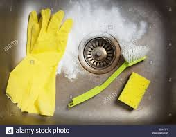 cleaning products and rubber gloves in a kitchen sink stock