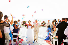 Beach Outdoor Wedding Ceremony Bride And Groom Walking Down Aisle Guests Throwing Beachballs