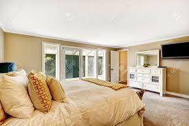master schlafzimmer im amerikanischen stil ausgestattet mit doppelbett und weiß waschbeckenunterschrank mit spiegel blick auf den balkon