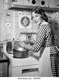 1950s HOUSEWIFE WEARING CHECKERED DRESS STANDING IN KITCHEN STIRRING POT ON STOVE LOOKING OVER SHOULDER