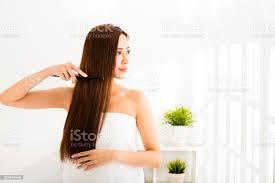 junge schöne frau kämmen ihr haar im wohnzimmer stockfoto und mehr bilder asiatischer und indischer abstammung