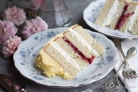 A slice of white layer cake filled with raspberry jam and whipped cream decorated in