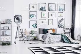 schwarz weiß teppich platziert auf dem boden im inneren der hellen schlafzimmer mit kingsizebett schwarz studio le und poster an der wand hängen