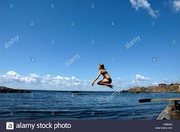 Side View Of A Girl Jumping Into The Sea From Diving Board