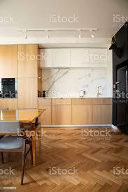 stilvolle und gemütliche skandinavische esszimmer und küche mit designfamilietisch stühlen und le weiße wände und braune holzparkett stockfoto und