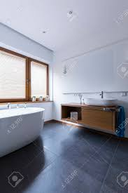 moderne badezimmer mit weißen wänden dunklen fliesen auf dem boden schneeweißen badewanne fenster und speichereinheit mit einem waschbecken