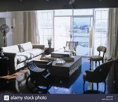 wohnzimmer mit sofa couchtisch und fensterfront mit