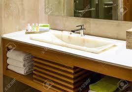 moderne marmor waschbecken in einer toilette oder hotel bad mit pflegeprodukten und frische handtücher