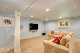 geräumige keller wohnzimmer interieur in pastellblautönen beige teppichboden und großen ecksofa mit tv northwest usa