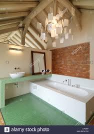 modernes bad im dachgeschoss mit holz decke und ziegel wand
