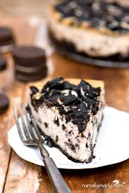A slice of vegan Oreo cheesecake sits on a white plate with a fork beside it