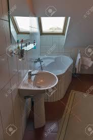 modernes weißes kleines badezimmer mit eckbadewanne waschbecken spiegel und fenster banska stiavnica slowakei